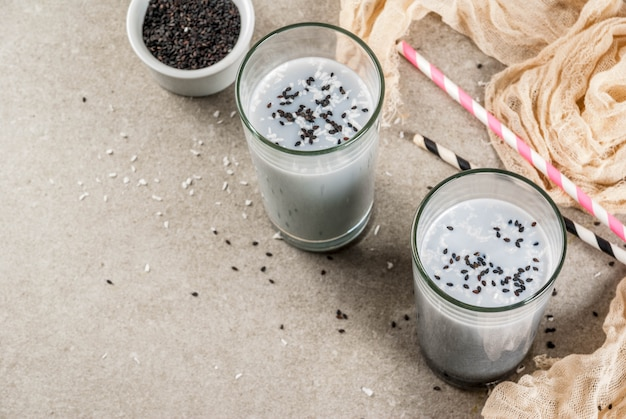 Trendy veganistische recepten, zwarte sesam iced latte of smoothie met sesamzaadjes, gedroogde kokos en amandelmelk, grijze stenen tafel, copyspace bovenaanzicht