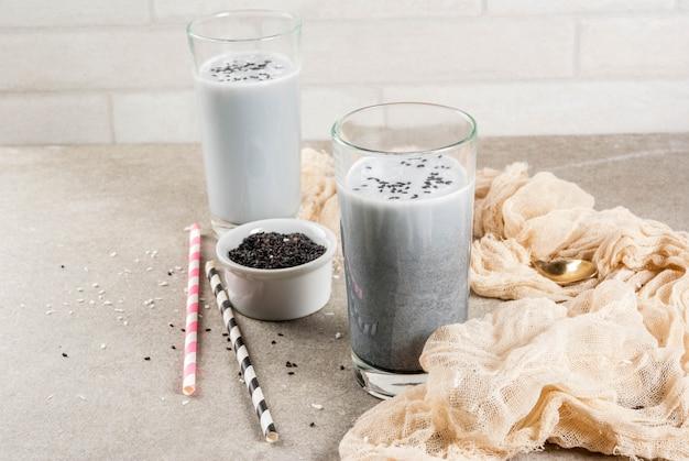 Trendy veganistische recepten, zwarte sesam iced latte of smoothie met sesamzaadjes, gedroogde kokos en amandelmelk, grijze stenen tafel, copyspace