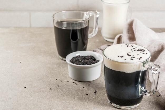 Trendy veganistische recepten, zwarte sesamcappuccino met sesamzaadjes en opgeklopte kokosmelk, grijze stenen tafel, copyspace