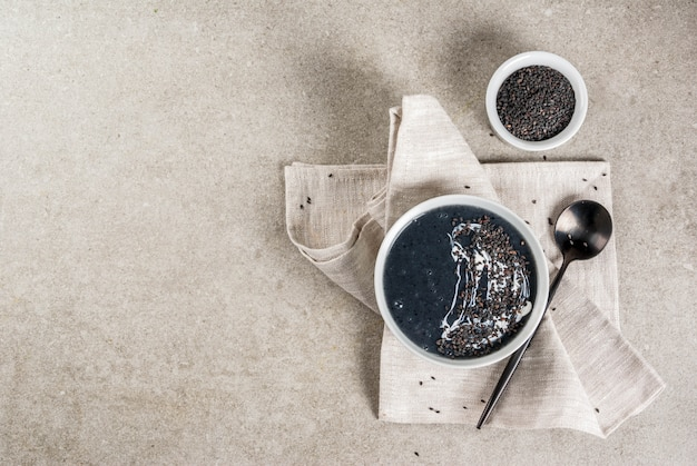 Trendy veganistische recepten, zwarte sesamsoep met sesamzaadjes en kokosmelk, grijze stenen tafel, copyspace bovenaanzicht