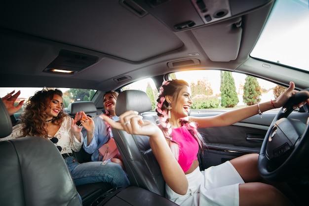 Trendy vrienden gaan in de auto naar muziek luisteren en samen plezier maken.