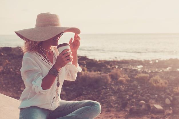 Trendy, vrolijke, mooie blanke vrouw met elegante hoed die geniet van een drankje in vrijetijdsbesteding in de buitenlucht met strand en oceaan