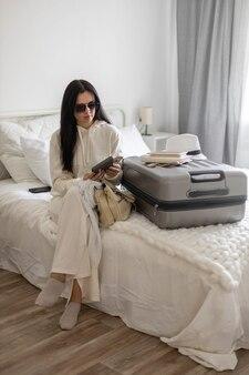 Trendy vrouw die het geld in de portemonnee controleert voordat ze de slaapkamer verlaat, klaar om te reizen