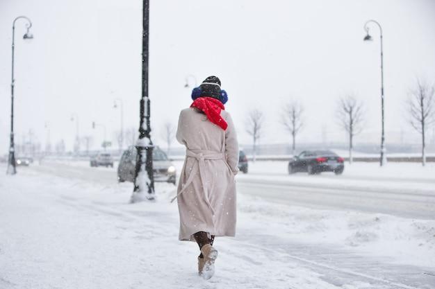Trendy vrouw in beige jas, rode sjaal lopen op lege straat tijdens sneeuwval