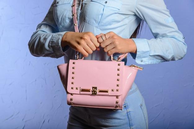 Trendy vrouw in jeans en denimoverhemd met roze handtas