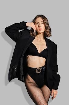 Trendy vrouw in slipje met hoge taille, blazer die haar wang aanraakt