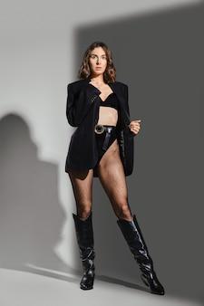 Trendy vrouw in slipje met hoge taille, blazer en lederen rijlaarzen poseren in studio