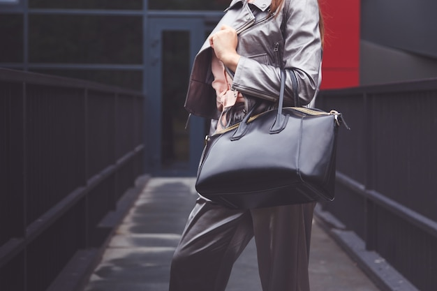 Trendy vrouw in zilveren broek jas met zwarte tas in de hand straat look. modieuze outfit