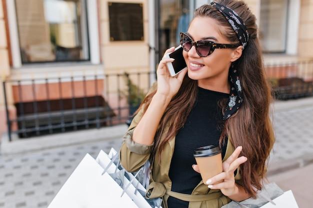 Trendy vrouw in zonnebril en lint koffie drinken tijdens het winkelen in het weekend