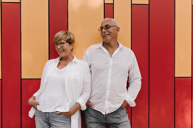 Trendy vrouw met blonde haren in lichte blouse en spijkerbroek lachen met grijze harige man in shirt met lange mouwen op rood en oranje.