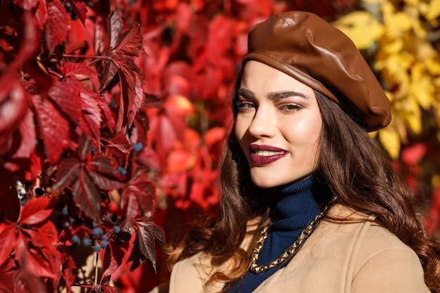 Trendy vrouw met een leren baret met lichte make-up die in de herfst tijd buitenshuis doorbrengt.