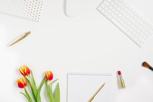 Trendy vrouwelijke thuiswerkplek. kantoor aan huis bureau met laptop, notebook, tulp, pen, accessoires en cosmetica op witte achtergrond. valentine plat lag, bovenaanzicht met kopieerruimte