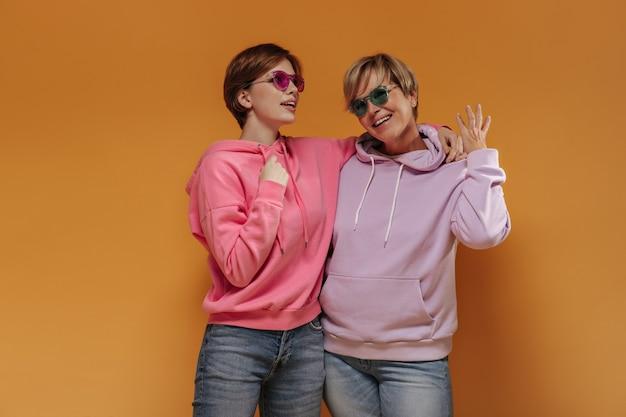 Trendy vrouwen met kort haar en heldere zonnebril in kleurrijke sweatshirt en coole spijkerbroek lachend op oranje geïsoleerde achtergrond.