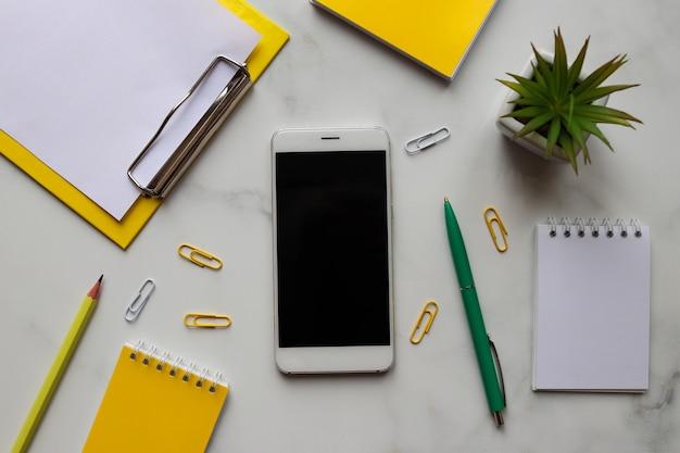 Trendy werkplek met notitieblokken, smartphone, potlood, pen en plant op marmer