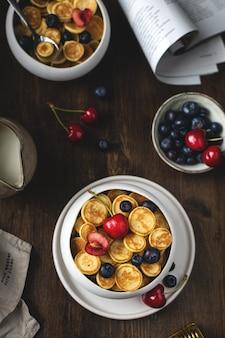 Trendy zelfgemaakt ontbijt, pannenkoekgranen, mini-pannenkoeken met bessen, bovenaanzicht