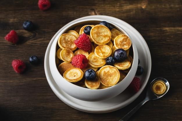 Trendy zelfgemaakt ontbijt, pannenkoekgranen, minipannenkoekjes met bessen