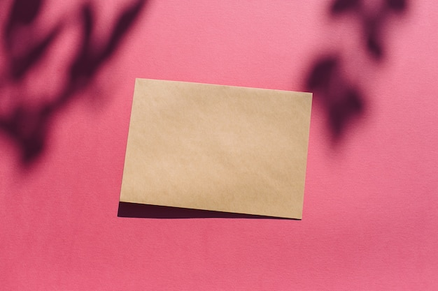 Trendy zomermodel gemaakt met horizontaal blanco kaartpapier op felroze zonovergoten achtergrond