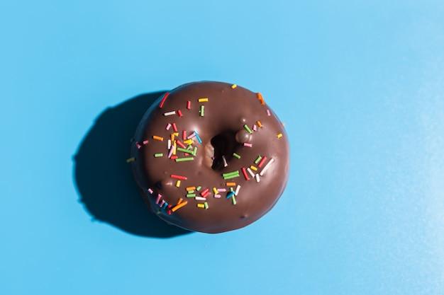 Trendy zonlicht. donut op heldere lichtblauwe turkooise achtergrond. minimaal zomerconcept. pop-art stijl. chocolade donut.