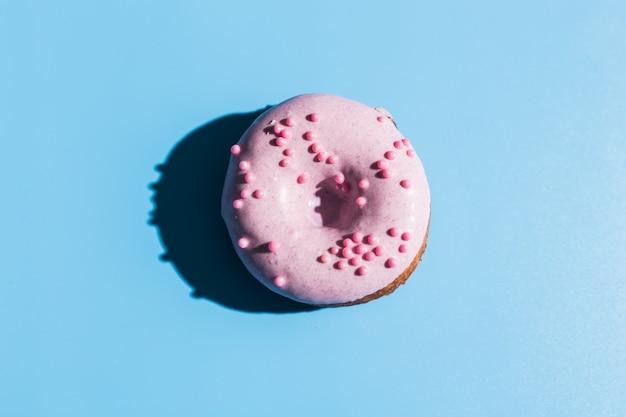Trendy zonlicht. donut op heldere lichtblauwe turkooise achtergrond. minimaal zomerconcept. pop-art stijl. roze donut.