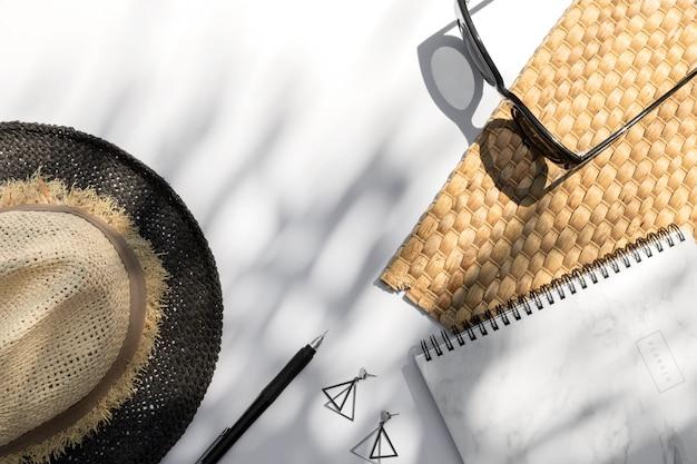 Trendy zonnebril, planner, hoed, oorbellen met palmbladschaduw op witte achtergrond