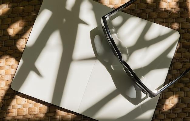 Trendy zonnebril, planner met palmbladschaduw op witte achtergrond