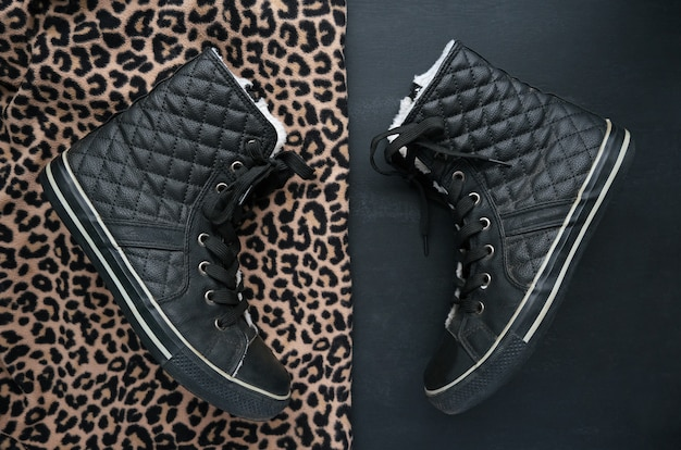 Trendy zwarte gewatteerde leren sneakers op twee contrasterende achtergronden. dierenprint en minimalistisch zwart. zwart en goud luipaard cheetah vlekken gestructureerde stof. mode schoenen schoeisel concept. flatlay.
