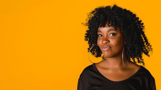 Trendy zwarte jonge vrouw op gekleurde achtergrond