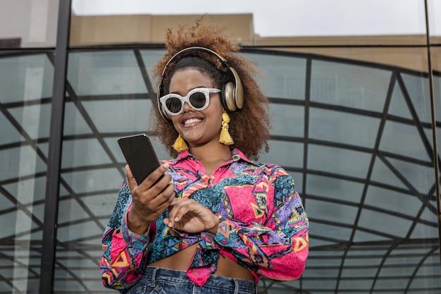 Trendy zwarte vrouw in hoofdtelefoon met behulp van sociale media op mobiel