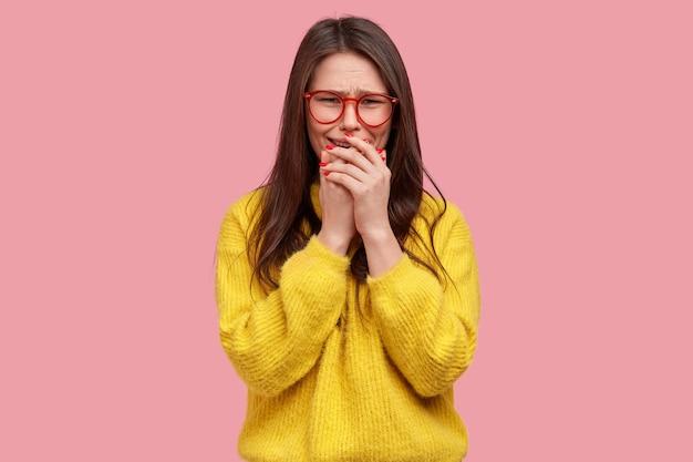 Treurig teleurgestelde vrouw bedekt mond met handpalmen, mokkend van spijt, wanhopig huilt, draagt bril en gele kleren