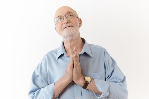 Treurige oude volwassen man in bril en blauw shirt met hoopvolle gezichtsuitdrukking, handen tegen elkaar gedrukt in gebed, in de hoop op het beste terwijl hij moeilijkheden, stress of problemen onder ogen ziet