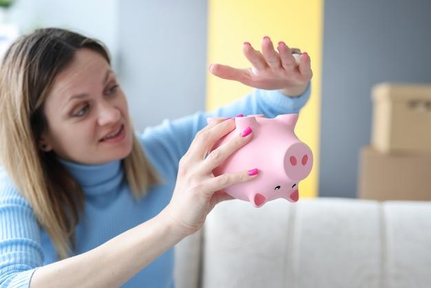 Treurige vrouw die haar hand op roze spaarvarken close-up slaat