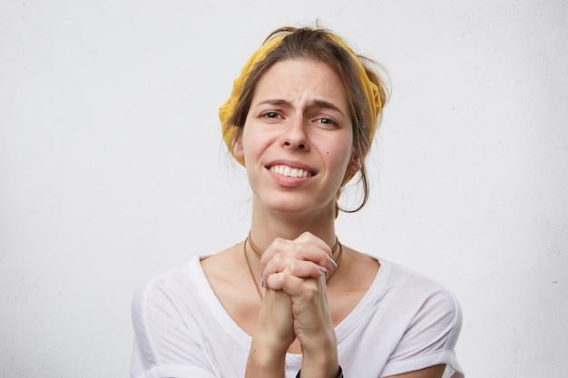 Treurige vrouw die haar handen bij elkaar houdt en haar man om vergeving vraagt en smeekt terwijl ze schuldig is.