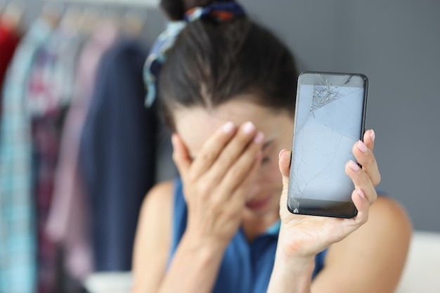 Treurige vrouw die haar ogen met de hand bedekt en kapotte mobiele telefoon close-up telefoonreparatie vasthoudt