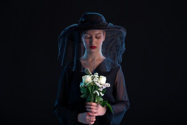Treurige vrouw gekleed in het zwart met bloemen op zwarte begrafenis dood verdriet
