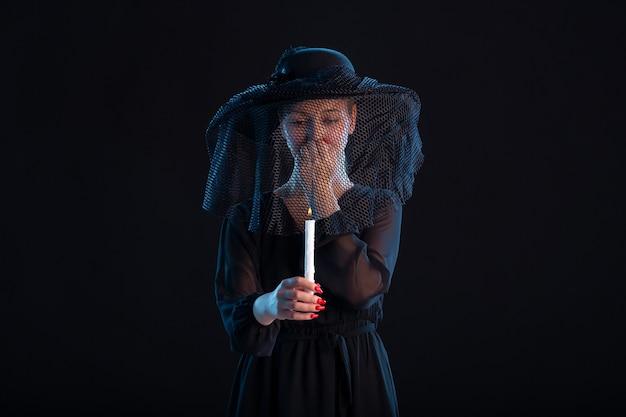 Treurige vrouw gekleed in het zwart met brandende kaars op de begrafenis van de zwarte dood
