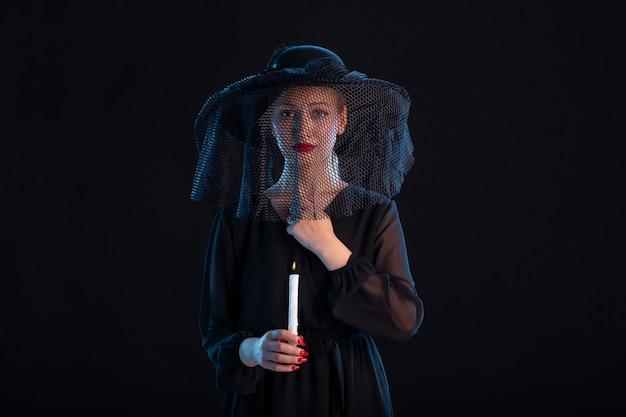 Treurige vrouw gekleed in het zwart met brandende kaars op een begrafenis met zwarte droefheid
