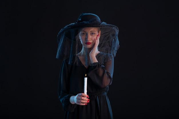Treurige vrouw gekleed in het zwart met brandende kaars op zwart bureau verdriet dood begrafenis