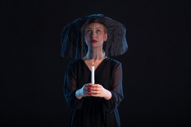 Treurige vrouw gekleed in het zwart met kaars op zwarte dood begrafenis verdriet