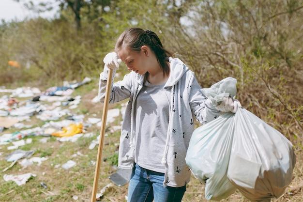 Treurige vrouw in vrijetijdskleding die vuilniszakken schoonmaakt die op een hark leunen voor het ophalen van afval in een bezaaid park