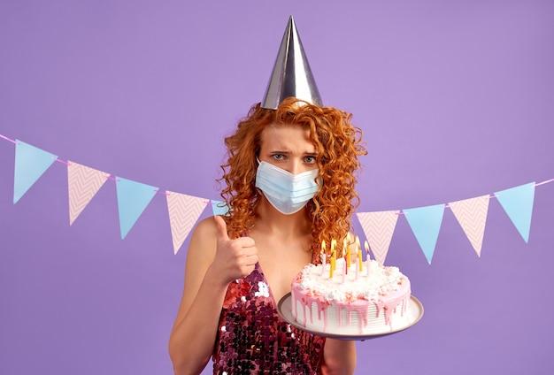 Treurige vrouw met een feestelijke pet en een beschermend medisch masker in een glanzende jurk heeft een taart geïsoleerd op paars