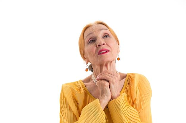 Treurige vrouw met gevouwen handen senior vrouw op witte achtergrond wens voor betere tijden