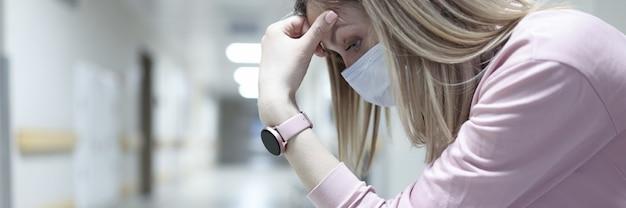 Treurige vrouw met medisch beschermend masker zit in de gang van de kliniek