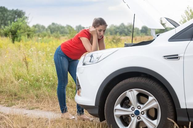 Treurige vrouw op zoek naar kapotte auto op het platteland
