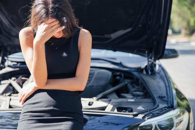 Treurige vrouw staande in de buurt van kapotte auto met open kap