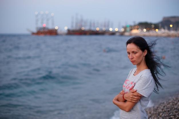 Treurige vrouw staat op het strand met lang haar