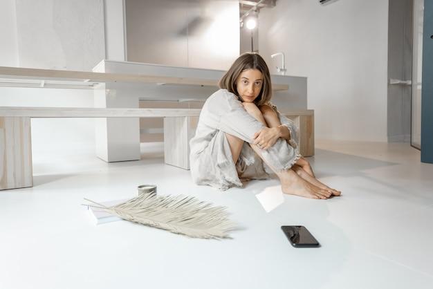 Treurige vrouw zit depressief alleen thuis