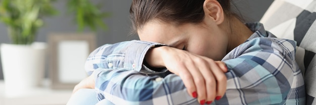 Treurige vrouw zit met haar hoofd gebogen op de sofa psychologische problemen concept