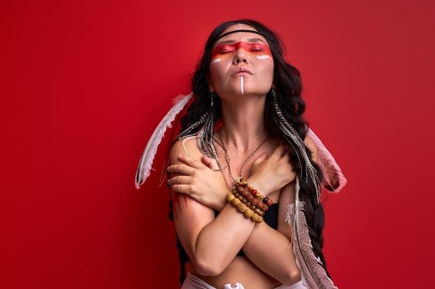 Tribale vrouw in sjamanistische kleding is sjamaan met gesloten ogen, geïsoleerd over rode muur, portret van etnische vrouw met tekeningen op lichaam