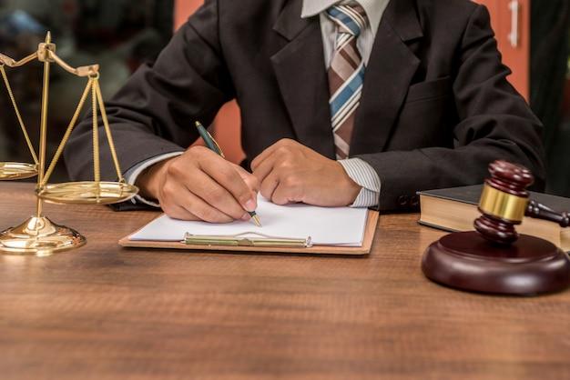 Tribunal procureuradvocaat die met documenten en houten hamer aan tabel in rechtszaal werken.