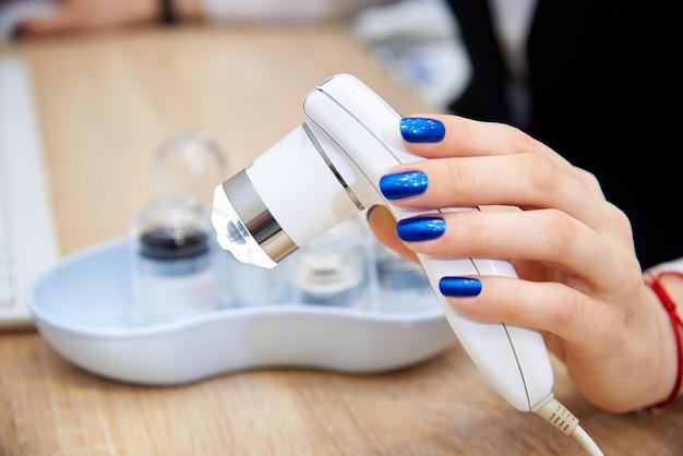 Trichoscope in een vrouwelijke hand.